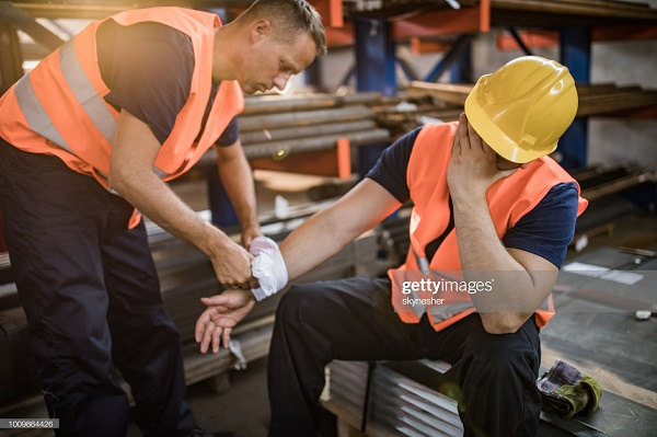 Manual worker feeling pain after having an injury at work while his colleague is helping him.
